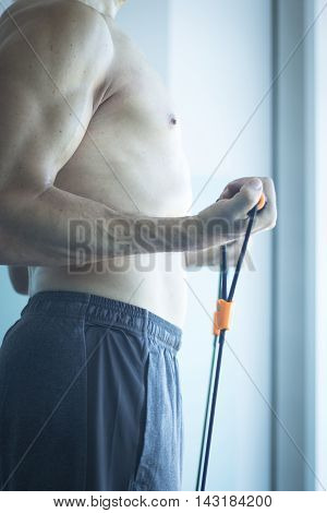 Man with muscular fit torsoand attractive body in 40's exercising with resistance exercise bands in sports club gym.