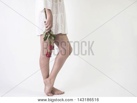woman standing barefoot in hand with roses and white dress, white background, color picture