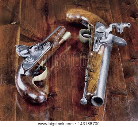 Real 18th century English flintlock pistols on wood background.