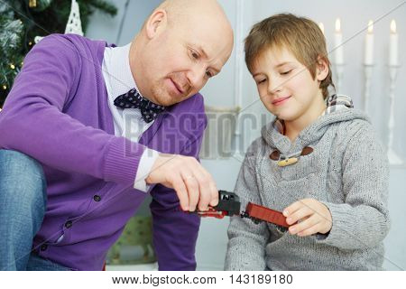 Father and son play with toy train near christmas tree, focus on man