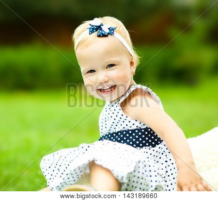 Little cute girl is playing her teddy bear outdoors