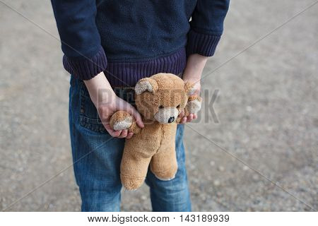 dramatic portrait of a little homeless boy with bear