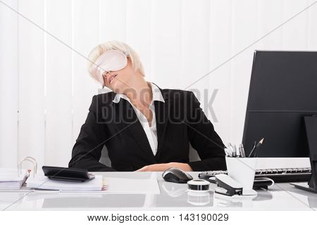 Young Businesswoman Wearing Eye Mask And Sleeping In Office