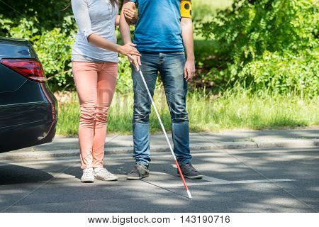 Woman Assisting Blind Man With White Stick On Street