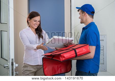 Friendly Delivery Man Handing Pizza To A Customer