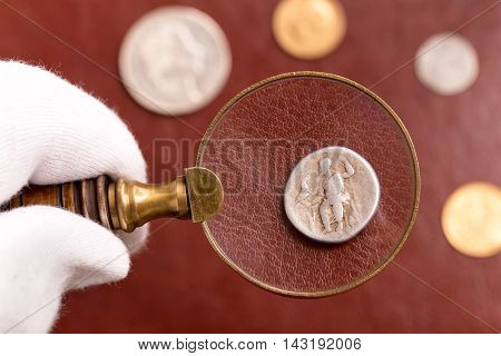 Examining antique Roman silver coin through magnifying glass on red leather surface
