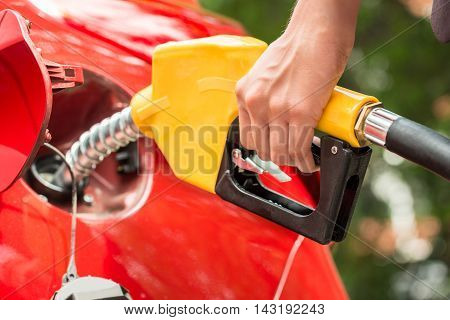 Close-up Of Businesswoman's Hand Refueling Car's Tank