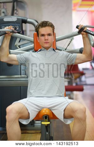 Young guy moving up and down his hands on fitness machine in fitness club
