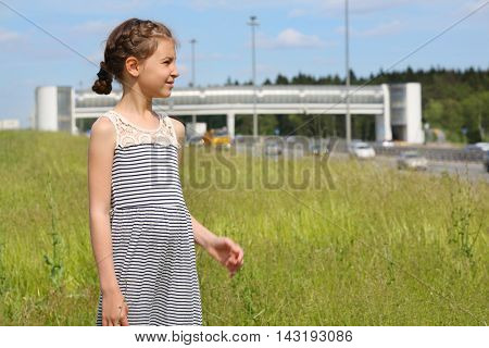 Cute girl stands on green grass and looks away near road at summer day