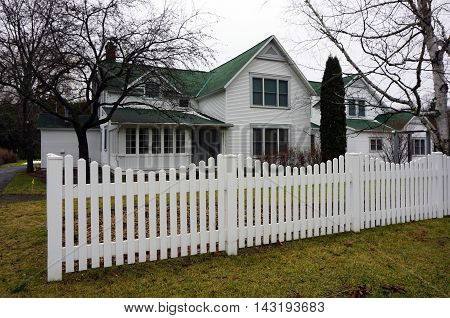WEQUETONSING, MICHIGAN / UNITED STATES - DECEMBER 22, 2015: A white picket fence stands in front of a home on Pennsylvania Avenue in Wequetonsing.