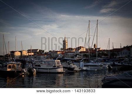 City of Rab, Croatia - August. 18, 2016: Ships in the port town of Rab in the background. Croatia is a gem, a popular destination for many tourists.