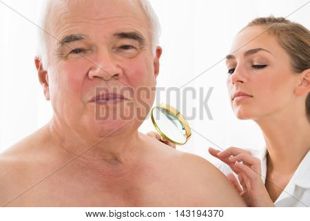 Young Female Doctor Examining Skin Of Senior Male Patient With Magnifying Glass