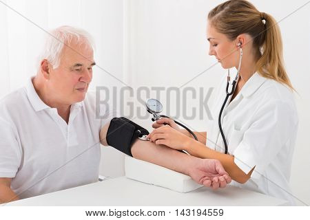 Young Female Doctor Checking Blood Pressure Of Senior Male Patient In Clinic