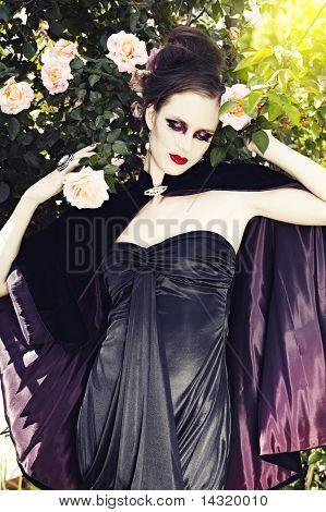 Woman In Velvet Cape In Rose Garden