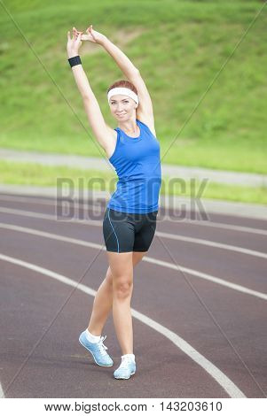 Young Caucasian Female Athlete Training on Sport Venue Outdoors. Vertical Image