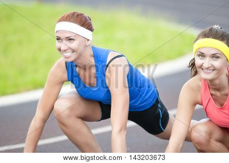 Portrait of Two Pretty Caucasian Sportswomen Having Fun Time At Sport Venue Outdoors.Horizontal Image