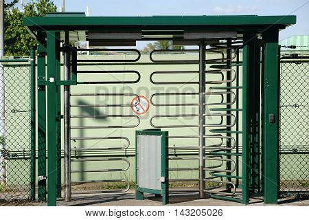 A rotary entrance from u-shaped bent metal pipes to an industrial area.