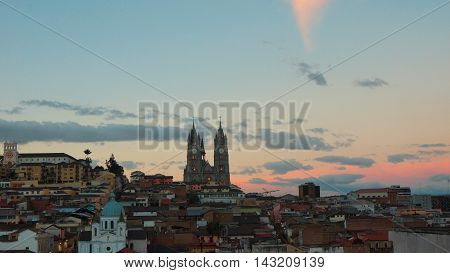 Quito Pichincha / Ecuador - August 16 2016: Sunset on historic center of Quito with Basilica del Voto Nacional in background. It was declared by UNESCO the first Cultural Heritage on 1978