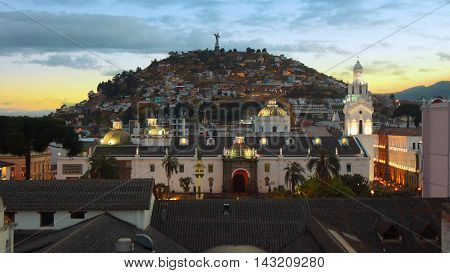 Quito Pichincha / Ecuador - August 16 2016: Sunset on Independence Square in the historic center with Virgen del Panecillo in background. It was declared by UNESCO the first Cultural Heritage on 1978