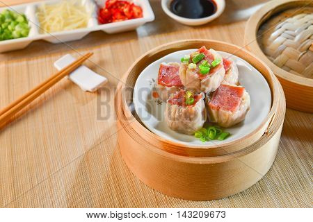 Dishes of ham dumplings on bamboo tray in asian restaurant