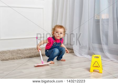 Little girl holding a mop in her hands. Little helper. Household chores.