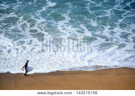 TORQUAY AUSTRALIA - JULY 202016 : surfer man on the beach with texture of turquoise-white water wave in the sea from top view at Bells beach Torquay Australia.