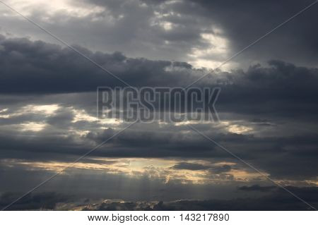 Beautiful sunset with dark storm clouds and glimpse of light