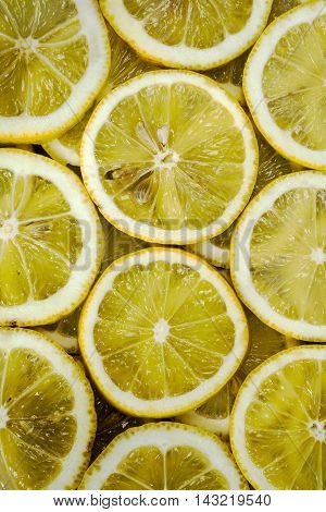 Some slices of ripe yellow lemons background