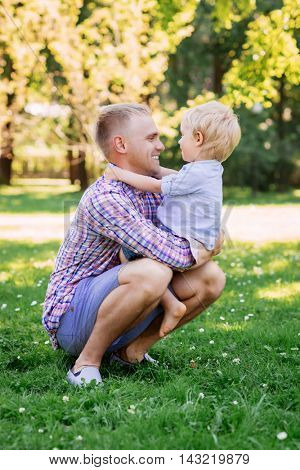 Young father sitting on haunches and playing with his son.