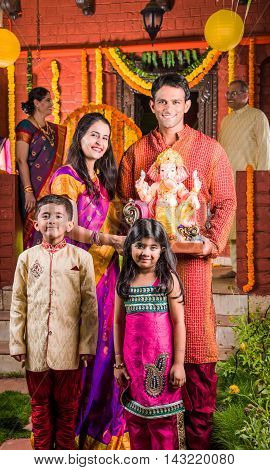 Smart Indian couple holding Ganesh idol or ganpati idol at entrance, welcoming lord ganesh on ganesh festival or chaturthi with kids and parents, happiness concept