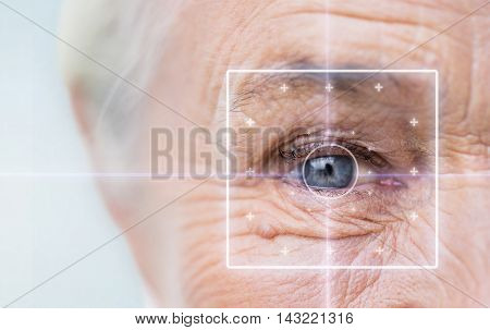age, vision, surgery, eyesight and people concept - close up of senior woman face and eye with laser light