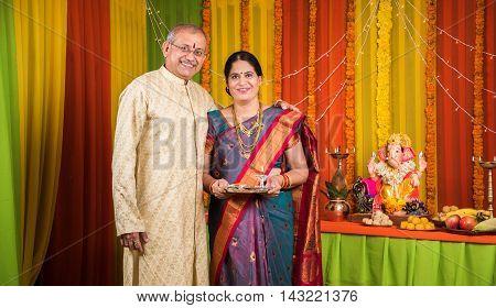 indian senior couple with puja thali performing puja on ganesh festival or ganesh utsav