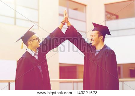education, graduation and people concept - smiling students in mortarboards and gowns making high five gesture outdoors