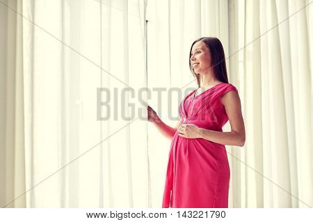 pregnancy, motherhood, people and expectation concept - happy pregnant woman with big tummy looking through window at home