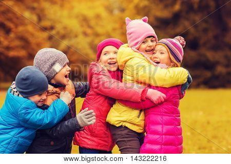 childhood, leisure, friendship and people concept - group of happy kids hugging in autumn park
