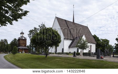 GRUNDSUNDA, SWEDEN ON JULY 22. View of a church, wooden belfry, cemetery on July 22, 2016 in Grundsunda, Sweden. Gravel path, walkways, gravestones this side. Editorial use.