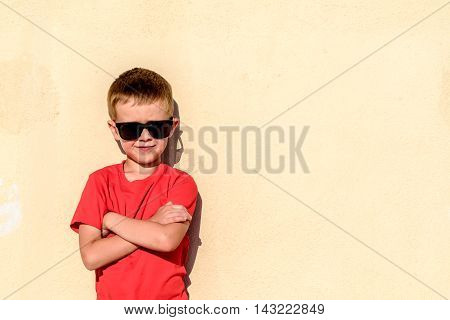 Portrait of young boy wearing sunglasses and leaning against wall like a boss