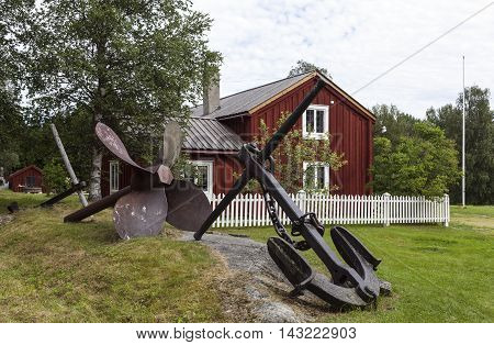 GRUNDSUNDA, SWEDEN ON JULY 22. View of a large black anchor and a rusty propeller this side an old homestead on July 22, 2016 in Grundsunda, Sweden. Lawn and an old homestead. Editorial use.