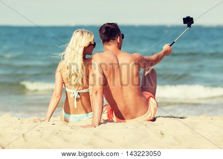 love, travel, tourism, technology and people concept - smiling couple on vacation in swimwear sitting on summer beach and taking picture with smartphone selfie stick from back