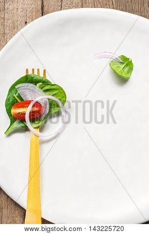 Spinach and Cherry tomato salad on yellow fork on a white dish