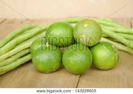 close up green lime and green yardlong bean on wood floor