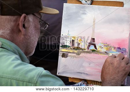 PARIS FRANCE - APRIL 20 2015: An artist drawing at Place du Tertre an open-air workshop with its 288 official painters on Montmartre