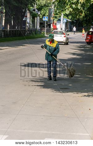 Janitor in overalls with a broom is engaged in cleaning the city streets.
