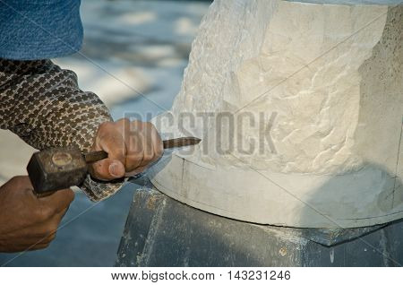 Man with hammer working on stone statue