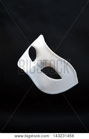 Theater concept. Closeup of white classical carnival mask on dark