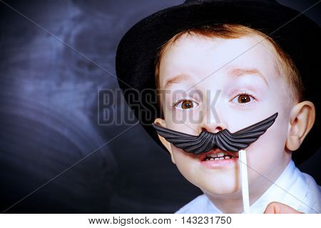 Funny little boy in father's hat plays with false mustache. Childhood concept. Emotions.