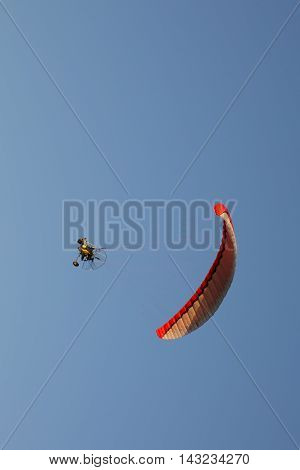 Motorised Paraglider Flying Over Mountains In Summer Day