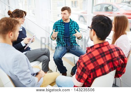 Therapist speaking to a rehab group at therapy session poster