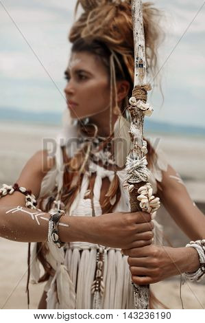 Attractive wild boho woman in white tribal dress portrait