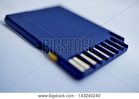 Isolated plastic compact memory card (SD card - Secure Digital card) used in cameras, computers and video cameras in a blue color with metal connectors in the golden color